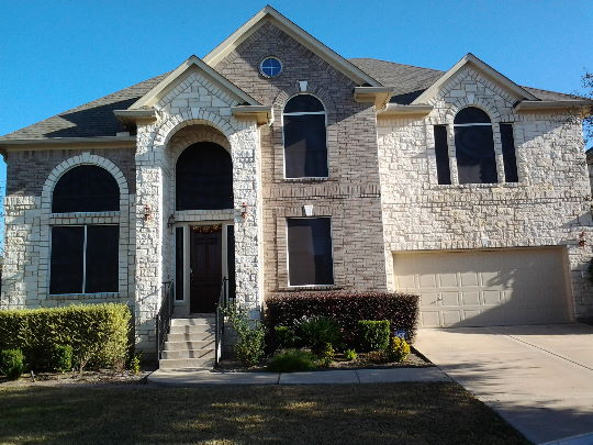 this austin tx home has a brown and white stone exterior with tan trim whereby the chocolate solar screen fabric was chosen as a perfect choice to